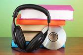 Turkuaz zemin üzerine ahşap masa kitap üzerinde kulaklık — Stok fotoğraf