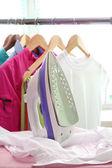 Plancha eléctrica y la camisa, sobre fondo de tela — Foto de Stock