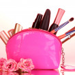 Make up bag with cosmetics and brushes on pink background — Stock Photo