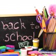 The words 'Back to School' written in chalk on the small school desk with various school supplies close-up isolated on white — Stockfoto #12339645