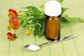 薬瓶の錠剤と竹のマットの上の花を持つ — ストック写真