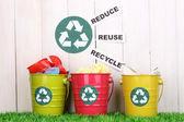 Reciclagem caixotes na grama verde, perto da cerca de madeira — Foto Stock