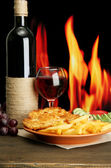 Roast chicken cutlet with french fries, glass of wine on fire background — Stock Photo