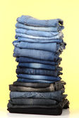 Many jeans stacked in a pile on yellow background — Stock Photo