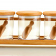 Empty glass jars for spices with spoons on wooden shelf isolated on white — Stock Photo