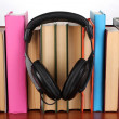 Headphones on books on wooden table on white background — Stock Photo