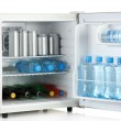 Mini fridge full of bottles and jars with various drinks isolated on white — Stock Photo #12363477