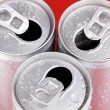 Aluminum cans with water drops on red background — Stock Photo