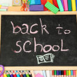 Royalty-Free Stock Photo: The words 'Back to School' written in chalk on the small school desk with various school supplies close-up