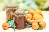 консервированные абрикосы и варенье в банки и спелые абрикосы в чашу на деревянный стол на зеленом фоне — Стоковое фото