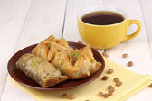 Sweet baklava on plate with tea on wooden background — Stock Photo