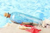 Bottiglia di vetro con nota all'interno sulla sabbia, su sfondo azzurro del mare — Foto Stock