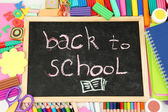 The words 'Back to School' written in chalk on the small school desk with various school supplies close-up — ストック写真