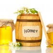 Sweet honey in barrel and jars with acacia flowers isolated on white — Stock Photo #12387604