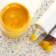 Brushes with colorful paint, tube with watercolor and jar with gouache on colorful splashes background close-up — Stockfoto