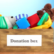 Donation box with children toys on blue background close-up — Stock Photo