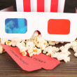 Popcorn with glasses and tickets on wooden table on grey background — Stock Photo