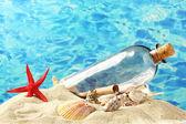 Glasflasche mit Hinweis innen auf Sand, blaues Meer Hintergrund — Stockfoto