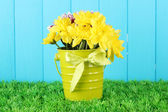 Beautiful bouquet of chrysanthemums in a bright colorful bucket on blue fence background — Stock Photo