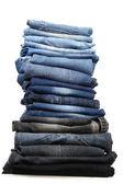 Many jeans stacked in a pile isolated on white — Stock Photo