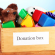 Donation box with children toys on blue background close-up - Stock Photo