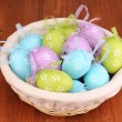 colorful easter eggs in basket on wooden background — Stock Photo #12392620