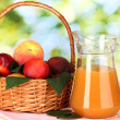 Ripe peaches in basket and juice on wooden table on natural background — Stock Photo