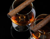 Two glasses of brandy and cigars on black background — Stock Photo