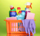 Basket with cleaning items on green background — Stock Photo
