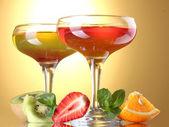 Frucht-gelee in gläsern und früchte auf gelbem grund — Stockfoto
