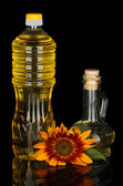 Sunflower oil in a plastic bottle and small decanter isolated on black background — Stock Photo