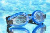 Blauwe zwemmen bril met druppels op blauwe zee achtergrond — Stockfoto