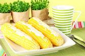 Gekochter mais mit butter auf einem grünen hintergrund — Stockfoto