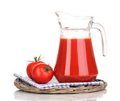 Tomato juice in pitcher on wicker mat isolated on white — Stock Photo