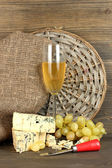 Composition of blue cheese and a glass of wine with grapes on wooden background close-up — Stock Photo