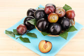 Rip plums on basket on wooden table — Stock Photo
