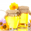 Sweet honey in jars and flowers isolated on white — Stock Photo