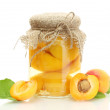 Canned apricots in a jar and sweet apricots isolated on white - Stock Photo