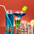 Variety of alcoholic drinks on red background — Stock Photo #12404641