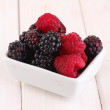 Ripe raspberries and brambles on wooden table - Stock Photo