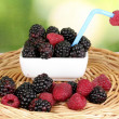 Ripe raspberries and brambles on nature background - Stock Photo