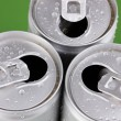 Aluminum cans with water drops on green background — Stock Photo