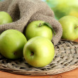 Ripe green apples with leaves on burlap, on wooden table, on green background — Stock Photo