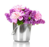 Beautiful lilac and peonies flowers in metal bucket isolated on white — Stock Photo