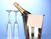 Champagne bottle in bucket with ice and glasses on blue background — Stock Photo