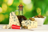 Composition of blue cheese and olives in a bowl on green background close-up — Stock Photo