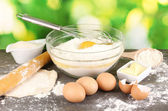 Eggs, flour and butter close-up on wooden table on natural background — Stock Photo