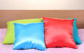 Bright pillows on bed on beige background — Stok fotoğraf