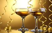 Gläser champagner und streamer auf gelbem grund — Stockfoto