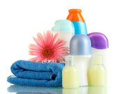 Cosmetics bottles with towel and flower isolated on white — Stock Photo